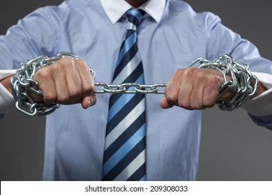 Man making streght against a chain. Selective focus on hands.