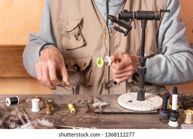 Man making trout flies. Fly tying equipment and material for fly fishing preparation .