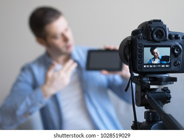 Man making video blog about tablet pc. Focus on camera.