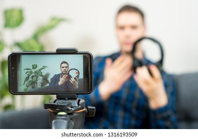 Man making video blog about music headphones.