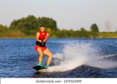 Man making waves on wakeboard