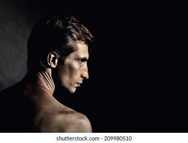 Man. Male portrait in profile on black background.