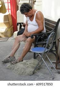 Man (Maltese) weaves a fishing net, September 19 2008, Malta, Editorial photo