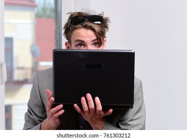 Man or manager with surprised sight in sunglasses. Cool guy wearing suit works on computer. Working online and gadgets concept. Businessman holds laptop on office window background, defocused