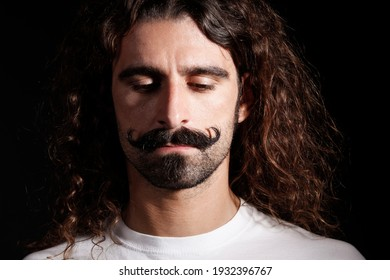 Man with manicured mustache and long hair looks down with distraught expression, isolated on dark background