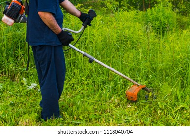 man with a manual lawn mower mows the grass