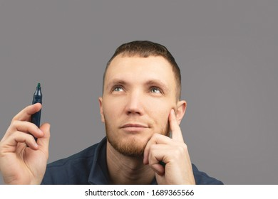 Man with marker in his hands is thoughtfully looking up on grey isolated background.