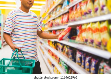 Man with a market basket shopping at the supermarket.