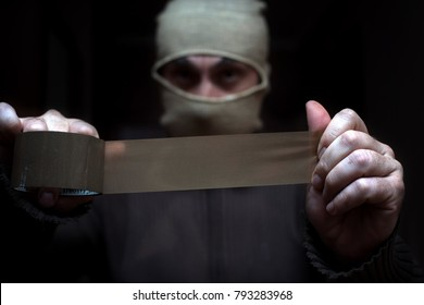 The man in mask and duct tape in his hands. The concept of kidnapping, robbery.