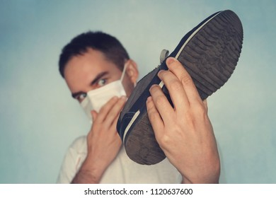 Man with mask is holding dirty stinky shoe - unpleasant smell concept, Dirty smelly sneakers. look at the sneakers