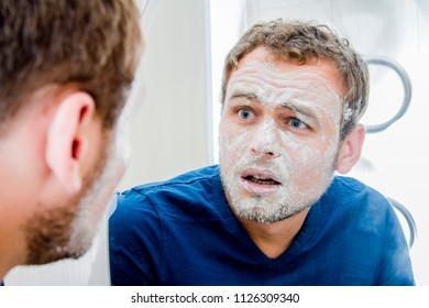 A man with a mask on his face against wrinkles looks surprised in the mirror