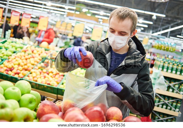 man in mask and protective gloves buying food in shop at coronavirus epidemic