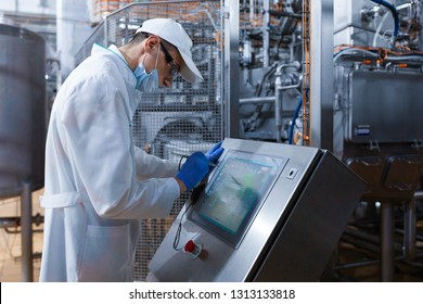 man in the mask and the robe works with the monitor to the Factory of dairy products