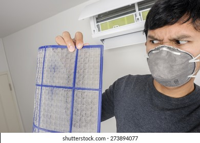 a man with mask showing dirty air filter before cleaning