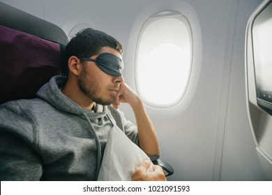 man in a mask for sleeping, sits in the airplane's chair near the porthole. Rest and comfortable flight in the plane.