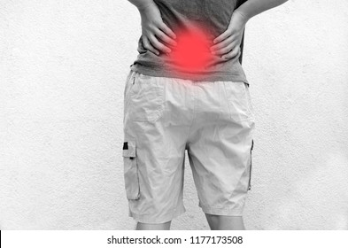 Man massage pain in low back spine.Standing and holding accent red painful spot.Spine health problem degenerative desease.Osteoporosis in youth
