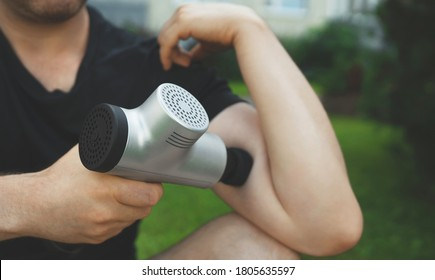 Man massaging his hand with massage percussion device after workout.