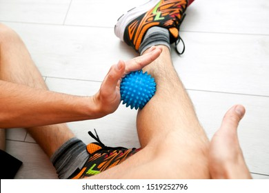 The man is massaging his leg by massage ball at home