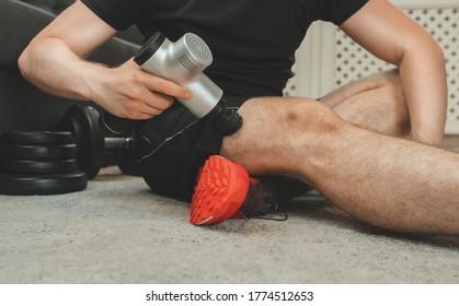 Man massaging leg with massage percussion device.