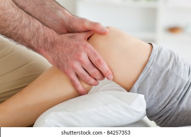 Man massaging a woman's knee in a room