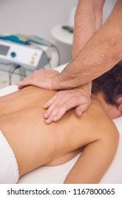 Man massaging a woman's neck in a room in physiotherapy clinic. Electrotherapy laser device. back being manipulated by an osteopath - an alternative medicine treatment