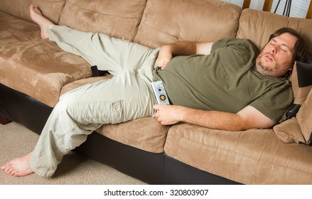 man mat falls asleep on the couch with his hands down his pants