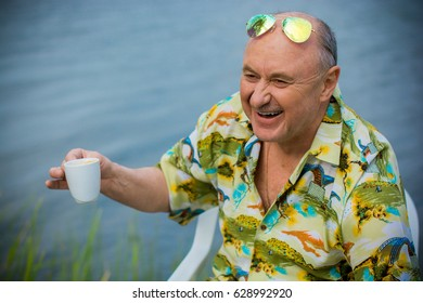 A man of mature age, American appearance, resting by blue lake in a Hawaiian shirt, straw hat and green glasses, a cheerful positive and emotional person