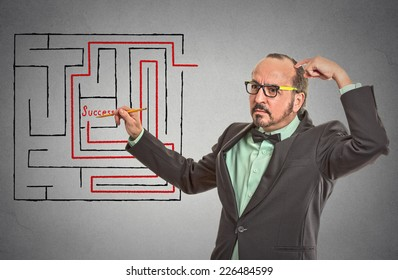 man maze success. drawing with pencil red path line through labyrinth to get success isolated grey wall office background. leadership guidance idea skill concept.Guy scratching head solving problem