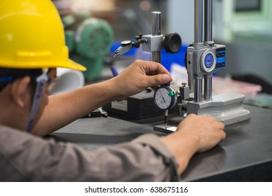 man measure part accuracy by dial guage
