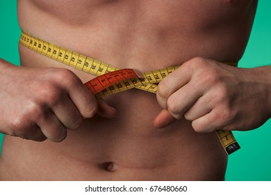 A man measures a body with a measuring tape on a green background