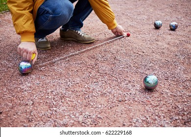 Man measures distance between balls during petanque game.