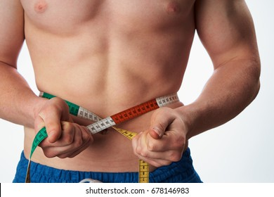 A man measures his waist with a measuring tape