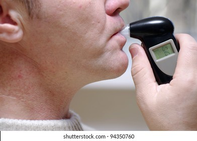 man measures the level of blood alcohol by Breathalyzer