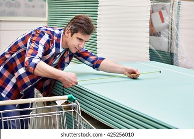 Man measures with roulette drywall sheets in the store building materials