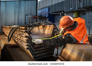 A man measures the size of a sheet pile Larsen. A worker at a construction site in a helmet fulfills his duties of sinking piles and complying with all standards.