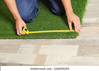 Man measuring artificial grass carpet indoors, closeup. Space for text