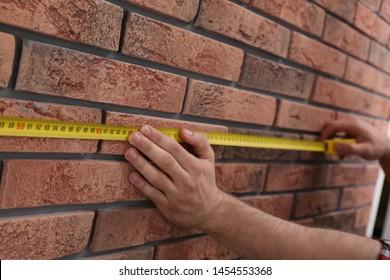 Man measuring brick wall, closeup. Construction tool