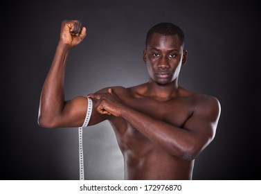 Man Measuring His Biceps With Measuring Tape On White Background
