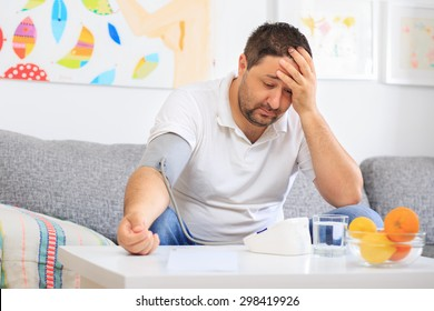 Man measuring his blood pressure holding his head and feeling sick