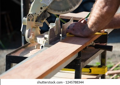 Man measuring a plank of wood outside in the sun