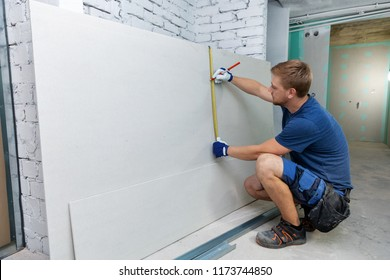 man measuring plasterboard sheet for interior construction