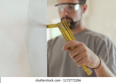 Man measuring a wall using a folding ruler: home renovation and construction concept