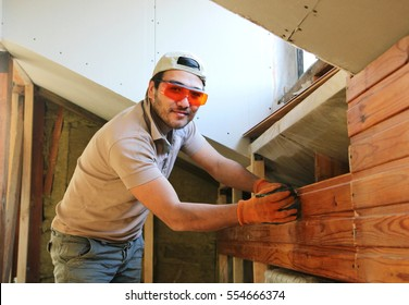 A man measuring wooden rail at home during construction - Shutterstock ID 554666374