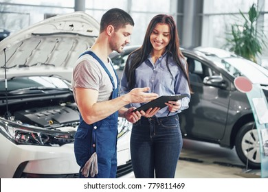 A man mechanic and woman customer discussing repairs done to her vehicle.