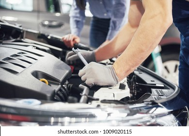 A man mechanic and woman customer look at the car hood and discuss repairs.