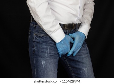 A man in medical gloves holds on to the groin, pain in the perineum, prostatitis