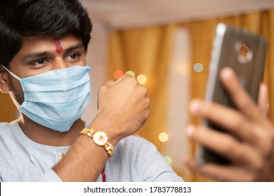 Man in medical mask busy on mobile phone and showing Rakhi or RakshaBandhan to sister or family friends at festival ceremony during coronavirus or covid-19 pandemic at home with decoration lights