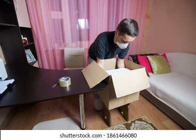 A man in a medical mask and gloves puts things in a cardboard box. Moving to a new place of residence during a pandemic.