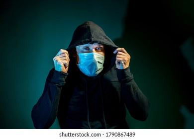 A man in a medical mask with a hood on his head poses on a dark green background