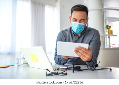 Man in a medical mask at the office. Man works remotely. The guy uses a tablet PC and a laptop for work, and medicine mask and antiseptic for self protective. Coronavirus pandemic, influenza, covid19